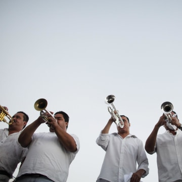 "Image: A brass band plays songs known to be favorites of Joaquin ""Chapo"" Guzman during a march in Culiacan"