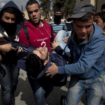 Image: An injured Palestinian man is evacuated toward an ambulance