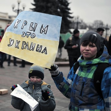 "Image: People hold a sign reading ""Crimea is Ukraine"""
