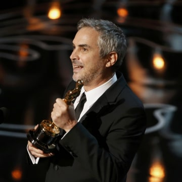 """Image: Alfonso Cuaron accepts the Oscar for best director for """"Gravity"""" at the 86th Academy Awards in Hollywood"""