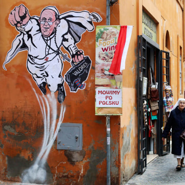 Image: A priest and a nun walk by a large drawing  of Pope Francis depicting him as a superhero on a wall near the Vatican