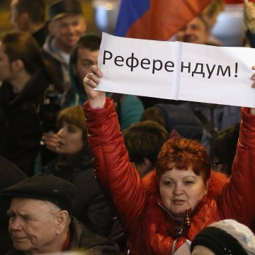 "Image: Pro-Russian sympathizers, including one woman holding a sign that says ""Referendum"""