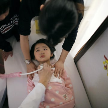 Image: A doctor conducts a thyroid examination on five-year-old girl