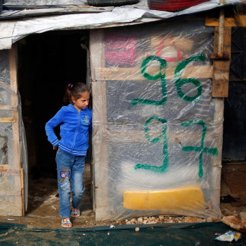 Image: A Syrian refugee child stands outside her shack in the Fayda Camp, some 25 miles east of Beirut