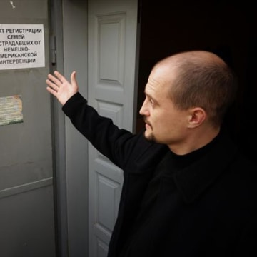 "Alexei Borsuk gestures toward signs in the PLM offices. The sign on the right says, ""Registration point for families suffering from the German-American intervention."" With a smile, Borsuk adds: ""I politicized that one a bit."""