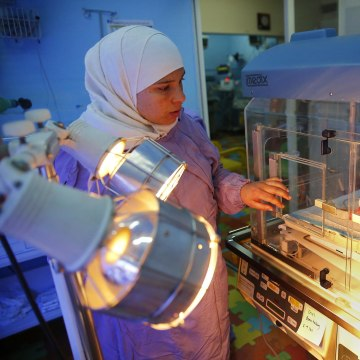 Image: Ahed Hussein, 18, puts her hand on the incubator where her premature newborn daughter rests