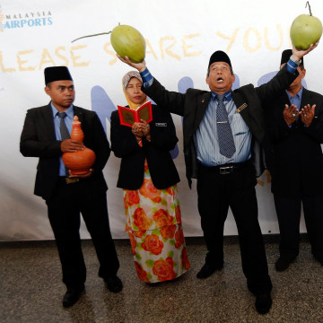 Image: Mat Zin, a local well-known shaman, holds two coconuts as he performs a ritual to help finding missing Malaysia Airlines jet at Kuala Lumpur International Airport