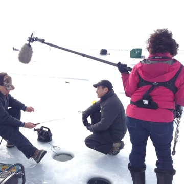 Image: John Yang interviews Minnesota resident Dave Maki, second left, who is ice fishing