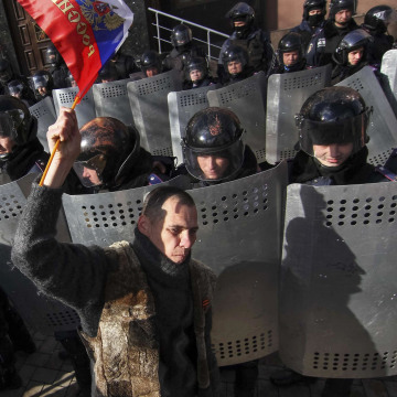 Image: Demonstrator takes part in a pro-Russian rally as riot police stand guard in Donetsk