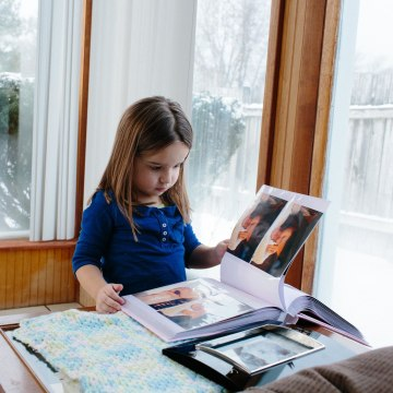 Image: Isabella looks through a scrapbook with images of Sophia