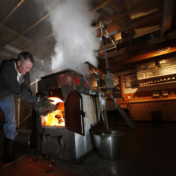Image: Paul Boulanger tosses wood in to fire up the sap evaporator at the Turtle Lane Maple sugar house in North Andover, Mass. on March 13.