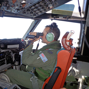 Image: A Royal Australian Air Force pilot of an AP-3C Orion maritime patrol aircraft scanning the surface of the sea near the west of Peninsula Malaysia