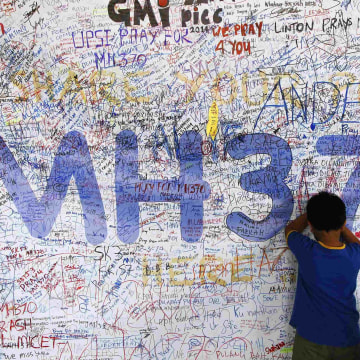 Image: Children write well-wishes on a banner for the missing Malaysia Airlines Flight MH370 at Kuala Lumpur International Airport