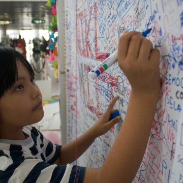 Image: People writing messages for the passengers aboard missing Malaysia Airlines flight MH370 at the international airport in Kuala Lumpur.