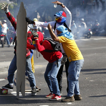 Image: Anti-government protesters take cover from the police behind makeshift shields in Caracas