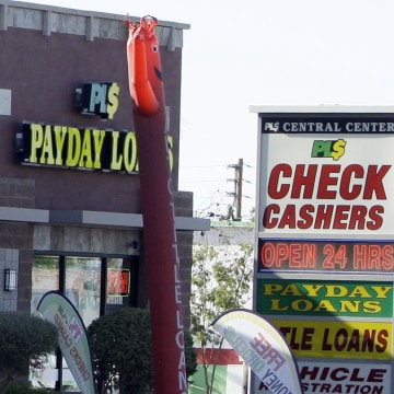 Image: Payday loan businesses advertise their services in Phoenix, Ariz.