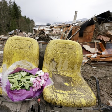 Image: Flowers are left on debris next to a demolished home where a woman's body was found following a deadly mudslide