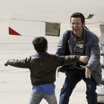 Image: Spanish reporter Javier Espinosa, reacts as his son Yerai runs towards him upon his arrival at the military airport of Torrejon in Madrid