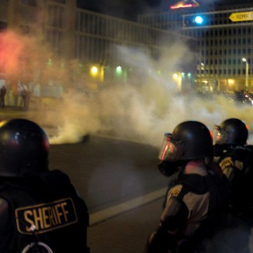 Image: Riot police launch tear gas toward protesters in downtown Albuquerque