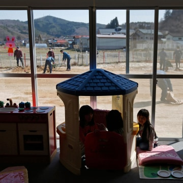 Image: Children play inside a playroom as TEPCO volunteers removed ice and snow and levelled dirt in their playground, at a Miyakoji child care center at Miyakoji area in Tamura
