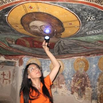 Image: UCLA archaeologist Ioanna Kakoulli examines a painting in the monastery under UV light