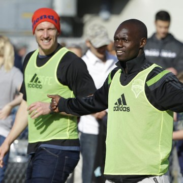 Image: Seattle Sounders' Micheal Azira, right, of Uganda, stands with Sounders' Kenny Cooper, left, during a pickup soccer match