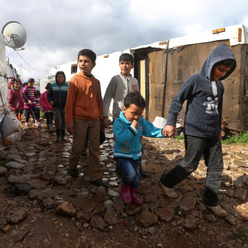 Image: Syrian refugee children walk between their tents on their way to a makeshift school