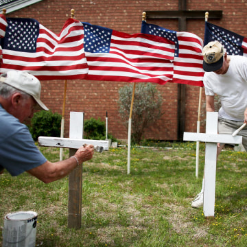 Image: Bob Gordon, left, and Bob Butler paint crosses they placed in front of 16 American flags as they build a memorial in front of Central Christian Disciples of Christ church for the victims of yesterday's shooting at Fort Hood