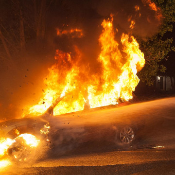 Image:  A firefighter tries to put out a fire in a car