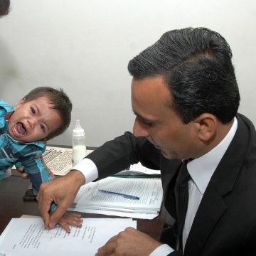 Image: A Pakistani lawyer taking the thumb impression from nine-month-old toddler Mohammad Musa Khan