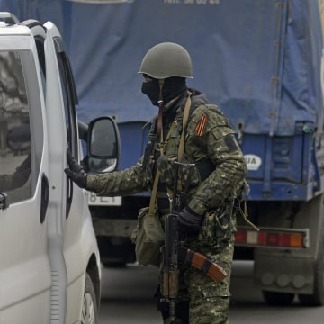 Image: An armed man inspects a car at an improvised checkpoint in Slaviansk
