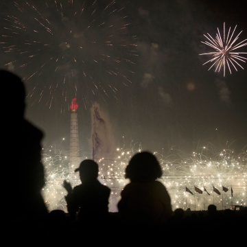 Image: North Korean children sit on the shoulders of their parents at Kim Il Sung Square in Pyongyang to watch fireworks over Juche Tower to celebrate the official birthday of the late leader Kim Il Sung on Tuesday