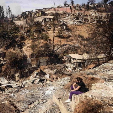 Image: A resident whose home was destroyed by major fire sits amid destruction in Valparaiso