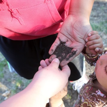 Image: Jaime Grimes son Kevin, 13, shows his sister Olivia, 3, dirt from the community garden they will plant this summer to supplement their food supply in Lincoln, Nebraska.