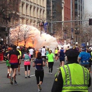 Image: Runners run towards the finish line as an explosion erupts at the finish line of the Boston Marathon