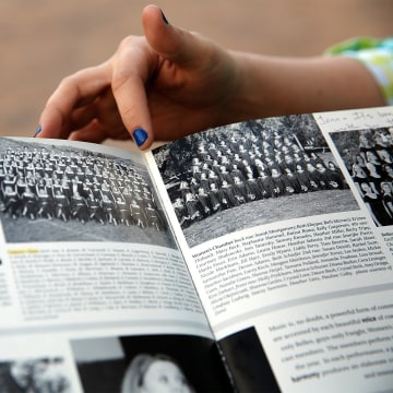 Image: Former Columbine High School student Jennifer Hammer points out the choir group picture in her yearbook to Heather Egeland at the Columbine Memorial