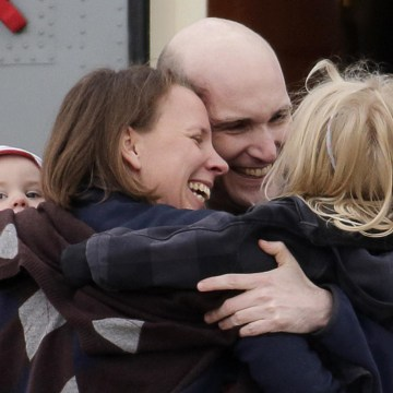 Image: French journalist Henin, former hostage, is greeted by his family moments after arrival of four former hostages by helicopter from Evreux to military airbase in Villacoublay, near Paris
