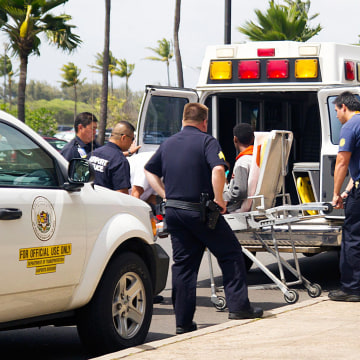 Image: The teenage boy who stowed away in the wheel well of a flight from San Jose to Maui is loaded into an ambulance at Kahului Airport.