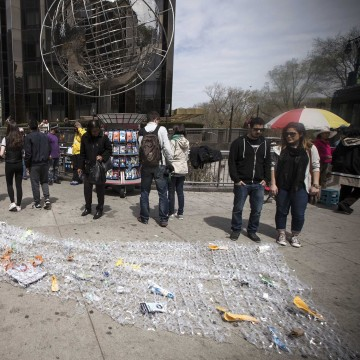 Image: Bianca Cortinas carries a sheet of plastic six pack rings and trash during a demonstration to mark Earth Day in Manhattan in New York City