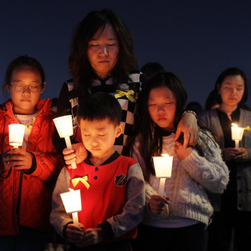 Image: Students and citizens hold candles as they pray for the missing passengers on the doomed South Korean ferry