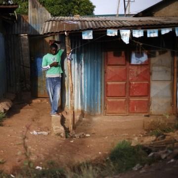 Image: A man checks his phone in Kibera, Kenya