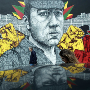 Image: People walk past a mural showing army captain Salgueiro Maia in Lisbon