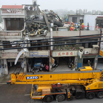 Image: Rescue workers lift a damaged AH-64E Apache attack helicopter from a roof in Taoyuan