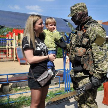 Image: A woman talks to an armed man in military fatigues