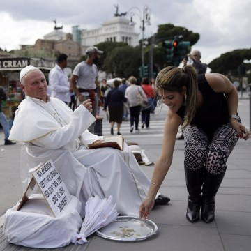 Image: A tourist drops a coins near Plisko Julius, a Slovakian man impersonating the late Pope John Paul II, after posing with him for a souvenir picture