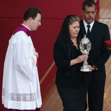 Image: Floribeth Mora holds the relic of Pope John Paul II