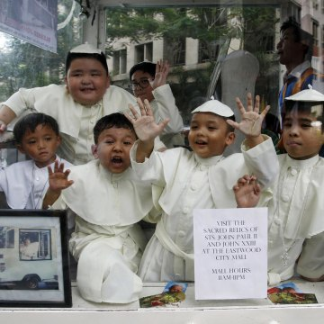 Image: Children wearing Pope's cassocks ride a Popemobile that was used by Pope John Paul II in his 1995 visit to Manila, during a parade in Quezon city