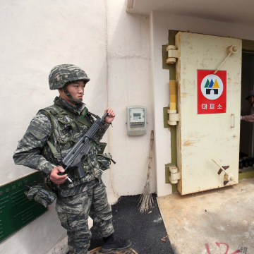 Image: A South Korean soldier stands watch as residents of Socheong Island evacuate to a shelter