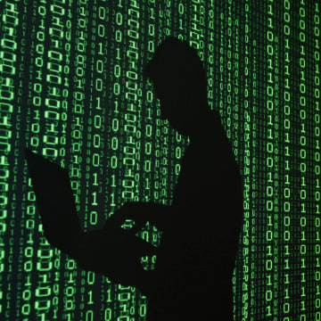 Image: Illustration of a projection of binary code around the shadow of a man holding a laptop computer