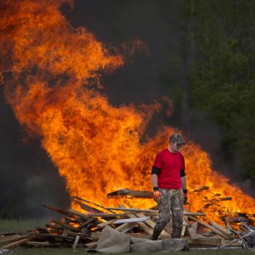 Image: Man walks away from a clean-up debris fire in Vilonia, Arkansas